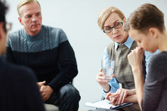 Mental Health Counselling in Support Group. Portrait of mature female mentor wearing glasses guiding psychological support group comforting young woman royalty free stock photo
