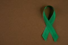 Mental Health. Green awareness ribbon on brown background. Symbol of Mental Health. Top vew with copy space Stock Photography