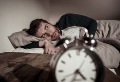 Young man in bed with alarm clock feeling desperate and distress not able to sleep with insomnia. Mental health, Insomnia and sleeping disorders. Frustrated and royalty free stock photos