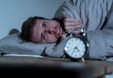 Young man in bed with alarm clock feeling desperate and distress not able to sleep with insomnia. Mental health, Insomnia and sleeping disorders. Frustrated and stock photos
