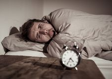 Young man in bed with alarm clock feeling desperate and distress not able to sleep with insomnia. Mental health, Insomnia and sleeping disorders. Frustrated and royalty free stock images