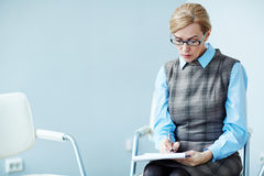 Mental Health Mentor. Portrait of mature woman wearing glasses sitting alone waiting for group therapy session to start and making notes royalty free stock photo