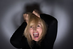 Mental Health Moment. Crazy, angry woman pulling hair out and screaming for mental health concept Royalty Free Stock Images
