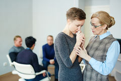 Mental Health Patient in Group Session. Portrait of mature female psychologist helping young women to stop crying, overcome fears and join group therapy session stock image