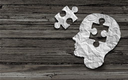 Mental Health Symbol. Puzzle and head brain concept as a human face profile made from crumpled white paper with a jigsaw piece cut out on a rustic old double Stock Image