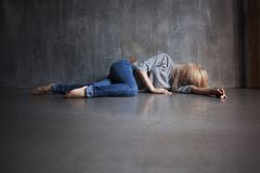 Mental health. Young woman lying on the floor stock image