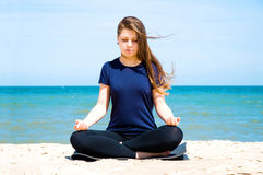 Mental health. Young woman practicing yoga at sea Stock Image
