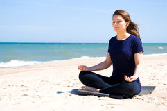 Mental health. Young woman practicing yoga at sea Royalty Free Stock Images