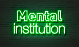 Mental institution neon sign on brick wall background. Stock Image