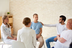 Mental Issues Support Group. Group of young people sitting in circle during therapy session, one men comforting other participant patting him on shoulder with stock image