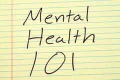 Mentala hälsor 101 på ett gult lagligt block Arkivfoto