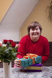 Mentally disabled woman holding many gifts Stock Image