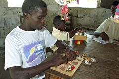 Mentally disabled Ghanaian boy is puzzling. Ghana, village Nkoranza: Portrait of a mental handicapped, Ghanaian boy during the lesson, in which he puzzles. So he Royalty Free Stock Image