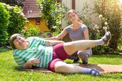 Mentally disabled woman is doing some assisted exercises. Mentally disabled women is doing some assisted exercises for her fitness Royalty Free Stock Photography