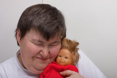 Mentally disabled woman with doll Stock Photography