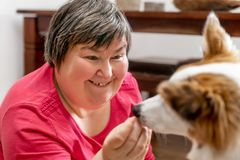 Mentally disabled woman is feeding a dog. Mentally disabled woman is feeding a funny dog, concept animal assisted living Stock Images