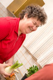 Mentally disabled woman in the kitchen is glad Royalty Free Stock Image