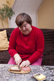 Disabled woman makes herself a sandwich Royalty Free Stock Photos