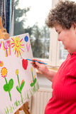 Mentally disabled woman painting a picture Royalty Free Stock Image