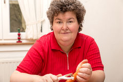 Mentally disabled woman is peeling carrots Stock Photos