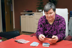 Mentally disabled woman playing cards, focus Royalty Free Stock Photography