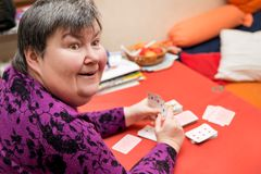 Mentally disabled woman playing cards, happiness and fun royalty free stock images