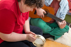 Mentally disabled woman playing a tambourine Royalty Free Stock Photography