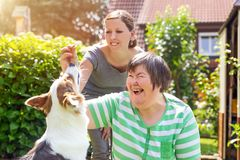 Mentally disabled woman with a second woman and a companion dog. Mentally disabled women with a second women and a companion dog, concept learning by animal stock photography
