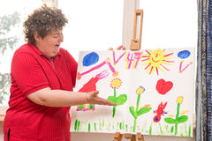 Mentally disabled woman showing her painting Royalty Free Stock Images