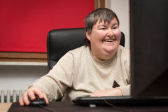 Mentally disabled woman sitting at the computer, Education and L Royalty Free Stock Photo