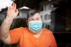 Mentally disabled woman with surgical mask waving out at a window, covid-19
