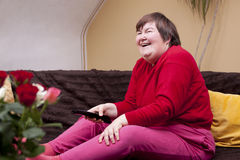 Mentally disabled woman watching television and enjoys Royalty Free Stock Photos