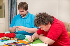 Mentally disabled woman and young man doing arts and crafts. A mentally disabled women and young men doing arts and crafts Stock Photo