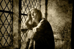 Mentally ill woman. Looking out of a window in a medieval building Royalty Free Stock Images