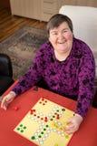 Mentalmente - la donna disabile è gioco a casa, giornalmente sistematico fotografie stock