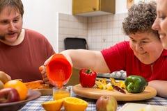 Mentalmente - mujer discapacitada y dos vigilantes que cocinan junto fotografía de archivo libre de regalías