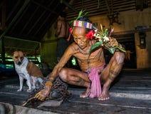 Mentawai plemienia mężczyzna siedzi w domu Zdjęcia Stock