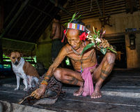 Mentawai tribe man sitting at home. MENTAWAI PEOPLE, WEST SUMATRA, SIBERUT ISLAND, INDONESIA – 03 OKTOBER 2011: Mentawai tribe man sitting at home royalty free stock photo
