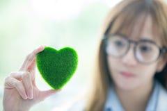 Mente do espírito do verde do whit da ciência Coração verde em sua mão no laboratório um fundo Doutor ou cientista fêmea de sorri imagens de stock