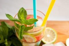 Menthe fraîche sur la table en bois avec les citrons et la limonade Photo libre de droits