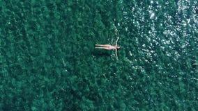 Mentira aérea de la mujer joven en superficie del mar almacen de video