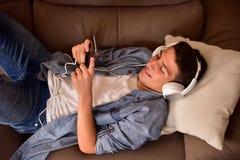 Mentira adolescente cara arriba en la opinión superior consumidora de las multimedias del sofá Fotografía de archivo libre de regalías