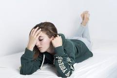 Mentira adolescente de 15 años en su cama Imagen de archivo libre de regalías