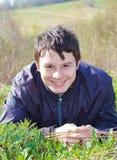 Mentira adolescente de risa en la hierba en primavera Imagen de archivo libre de regalías