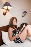 Mentira adolescente en cama y lectura Imagen de archivo