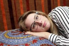 Mentira adolescente en el sofá Imagen de archivo