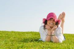 Mentira adolescente en la hierba que desgasta un sombrero púrpura agradable Fotografía de archivo libre de regalías
