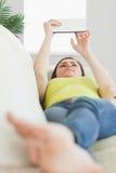Mentira adolescente feliz en un sofá usando una PC de la tableta Foto de archivo libre de regalías