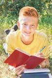 Mentira adolescente zurda y escritura en la hierba Foto de archivo