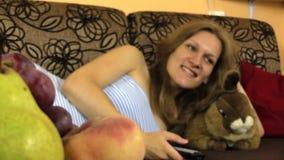 Mentira agradable de la mujer en magro del sofá el codo en el conejo del juguete, reloj TV almacen de video